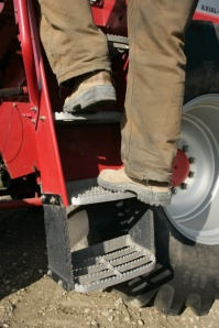 A worker climbs down the steps in a controlled fashion.  Wearing appropriate footwear and keeping the steps clear is also essential to avoiding slips and falls from machinery.  Credit: Alberta Farm Safety Program; Government of Alberta.